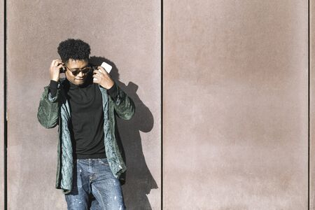 cool african black man with casual modern clothes and a mobile phone and headphones listening music leaning against wall, technology and lifestyle concept