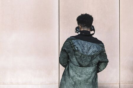 back view of a black man with headphones to listen music in front of a wall, technology and lifestyle concept