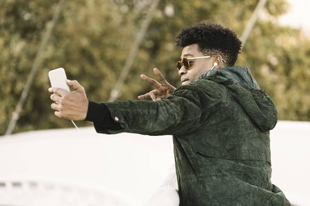 cool young african black man taking a selfie with smartphone and earphones while poses for the photo, city lifestyle and technology concept using internet electronic device Banco de Imagens