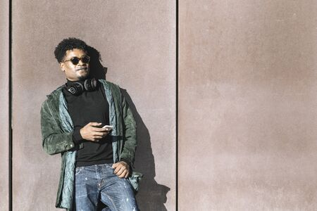 cool african black guy with casual modern clothes and a mobile phone and headphones to listen music leaning against wall, technology and lifestyle concept Banco de Imagens