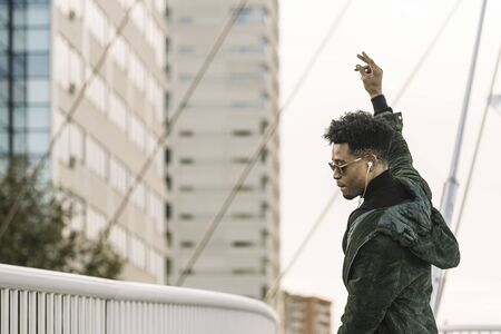 young attractive african black man with white earphones and sun glasses walking outdoor in the city having some fun and dancing, lifestyle and technology concept, copy space for text