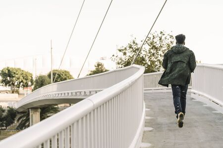 view from behind attractive young black african man with cool casual wear running on a modern bridge in the city, lifestyle concept Banco de Imagens