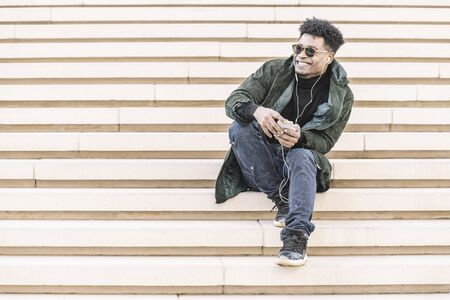 young black man with sunglasses in casual modern clothes sitting on stairs, listen to music of his phone in earphones while smile, technology and lifestyle concept