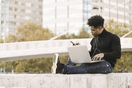 handsome black student with white earphones working with computer and smart phone sitting outdoors in the city at sunset, lifestyle and technology concept using internet electronic device