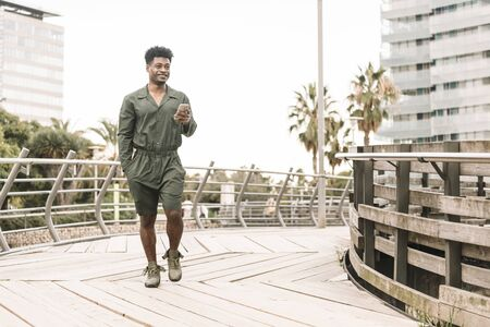 cool smiling african black man texting message on the phone while walks in a park outdoors in the city, lifestyle and technology concept, copy space for text Banco de Imagens