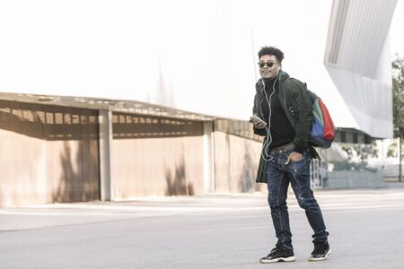 black young man with earphones walking by the city and listening music with a mobile phone, technology and lifestyle concept using internet electronic device outdoors