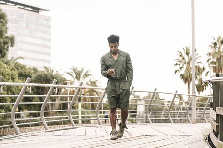 cool young african black man texting message on smartphone while walks in a park outdoors in the city, lifestyle and technology concept, copy space for text