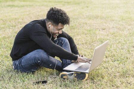 smiling young black man laughing with white earphones and phone working typing in a computer sitting on the lawn at park, lifestyle and technology concept using internet electronic device