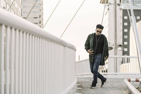 young stylish black man with white earphones and sun glasses dancing outdoor in the city having some fun, lifestyle and technology concept, copy space for text 스톡 콘텐츠