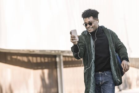 black young man with earphones making a video call with a mobile phone, technology and lifestyle concept using internet electronic device outdoors