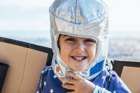 portrait of a funny little child girl laughing naughty disguised as a superhero with homemade costume, cardboard plane wings and astronaut helmet, imagination and girl power concept