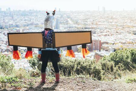 Rückansicht eines kleinen Kindermädchens, das als Superheld verkleidet ist, mit hausgemachtem Kostüm, Pappflugzeugflügeln und Astronautenhelm, der das Stadtbild, die Fantasie und das Mädchenpower-Konzept sieht