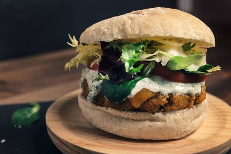 vegan burger with lettuce tomato and sauce on a wooden plate, vegetarian food and healthy lifestyle concept