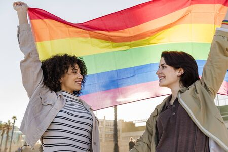 coppia interrazziale di ragazze sorridenti che sventolano la bandiera arcobaleno, simbolo della lotta per i diritti, concetto di libertà e diversità razziale