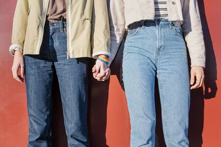 detail of two women linking hands with a bracelet in the colors of the rainbow flag, symbol of the struggle for homosexual rights, concept of sexual freedom and diversity
