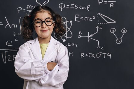 cheerful little girl science student with glasses in lab coat smiles on school blackboard background with hand drawings science formula pattern, back to school and successful female career concept
