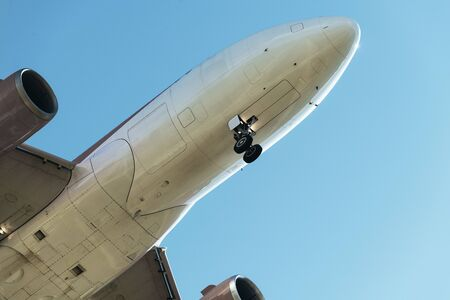 detail of the nose of a plane flying seen from below with the landing gear deployed, travel concept, copy space for text