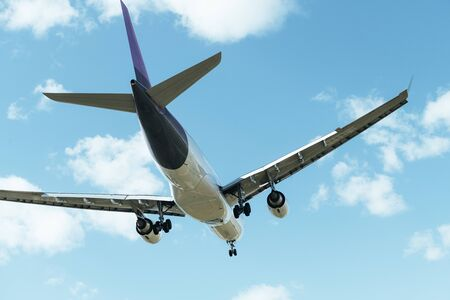 commercial aircraft flying seen from behind with the landing gear deployed, travel concept Stock Photo