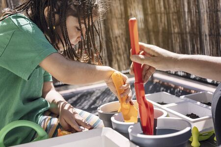 girl and her mother putting soil in the flower pots with a shovel at the balcony, hobbies at home, sustainable and ecological lifestyle concept