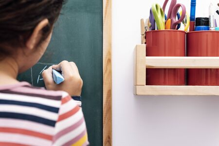 unrecognizable child drawing on a blackboard, drawing and craft concept at home