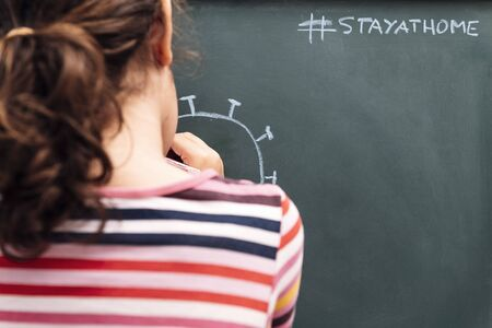 child drawing a coronavirus on a blackboard with the message, stay at home, concept of kids in quarantine, copy space for text