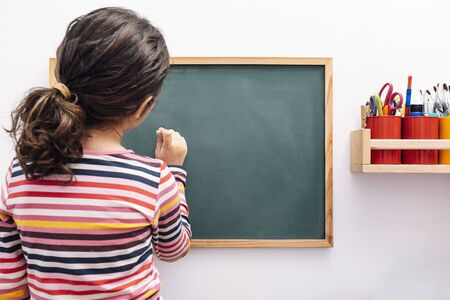 little girl drawing on a blank blackboard, concept of school and learning, copy space for text Banque d'images