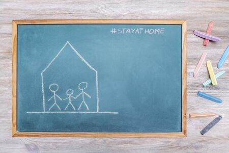 confined family drawn on a blackboard with the message stay at home and colored chalk next to it, concept of quarantine with children, copy space for text