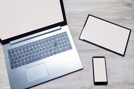 laptop, tablet and phone with blank screen on a wooden table, responsive design concept