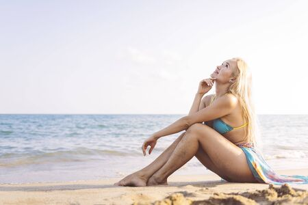 relaxed blonde girl sitting on the beach sand, summer vacation concept and disconnection