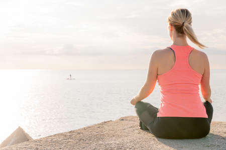 back of an unrecognizable blonde woman practicing yoga at sunrise sitting in the lotus position in front of the sea, concept of mental health and relaxation, copy space for text