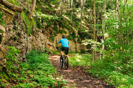 back view of an unrecognizable cyclist riding his mountain bike along a forest path, concept of sport and healthy lifestyle in nature