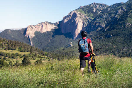 young man with backpack observes the landscape and the mountains standing next to his mountain bike in the countryside, concept of sport and healthy lifestyle in nature, copy space for text Foto de archivo