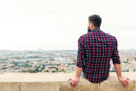 rear view of a bearded man sitting on the rooftop observing the city at his feet, concept of freedom and disconnection, copy space for text