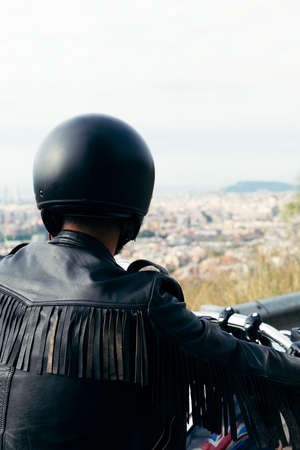 back view of an unrecognizable biker with helmet and leather jacket looking at the city from a viewpoint, concept of freedom and rebellious lifestyle, vertical photo