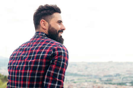 profile portrait of a handsome bearded man smiling, concept of beauty and masculinity, copy space for text