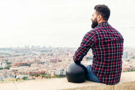 handsome bearded man sitting on the rooftop with a motorcycle helmet looking the city at his feet, concept of freedom and disconnection, copy space for text