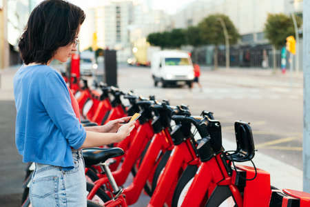 young woman using the phone to unlock a bike from the rental station, concept of ecology and sustainable mobility against climate change, copy space for text