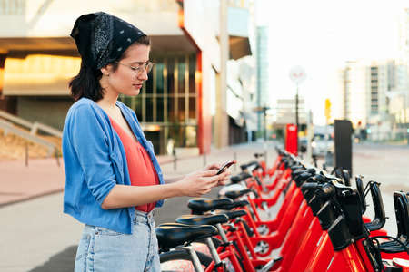 young woman using a smart phone next to an electric bike rental station in the city, concept of ecology and sustainable mobility against climate change, copy space for text
