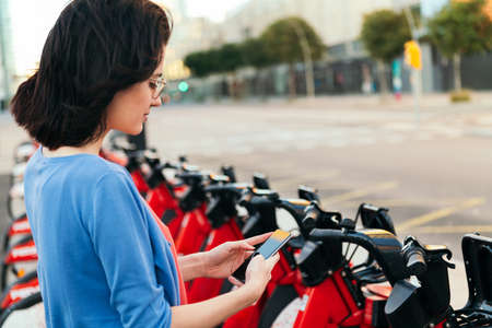 young woman consulting the phone next to an electric bike rental station in the city, concept of ecology and sustainable mobility against climate change, copy space for text