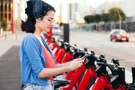 young woman using the phone next to an electric bike rental station in the city, concept of ecology and sustainable mobility against climate change, copy space for text