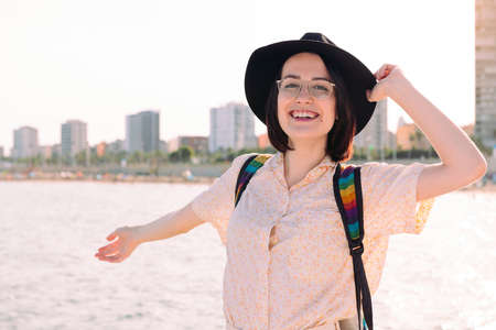 portrait of a young traveler woman with hat smiling happy near the sea next to the city, travel and tourism concept, copy space for text Archivio Fotografico
