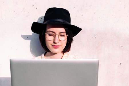 portrait of a young woman with hat working with laptop sitting against a gray wall, concept of digital nomad and blogging lifestyle, copy space for text