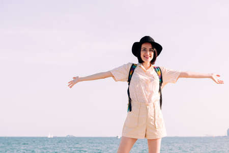 young traveler woman with hat smiling free and happy with her arms open in front of the sea, concept of travel and tourism, copy space for text Archivio Fotografico