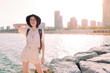 young traveler girl with hat smiling happy near the sea next to the city, travel and tourism concept, copy space for text