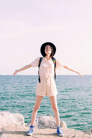 vertical photo of a young traveler woman with a hat smiling free and happy with her arms open in front of the sea, concept of travel and tourism, copy space for text