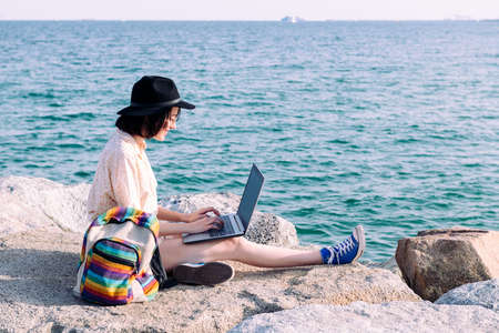 young traveler girl working with computer and backpack by the sea, concept of digital nomad and blogger lifestyle, copy space for text