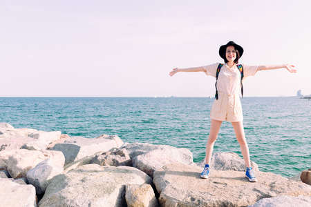 young traveler woman with hat smiling happily with open arms in front of the sea, concept of travel and tourism, copy space for text