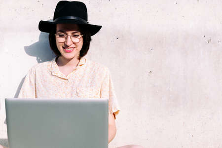 young woman with hat working with computer sitting against a gray wall, concept of digital nomad and blogging lifestyle, copy space for text Archivio Fotografico