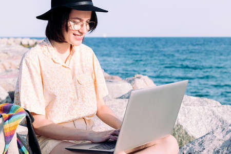 portrait of a young traveler girl working with laptop and backpack by the sea, concept of digital nomad and blogger lifestyle