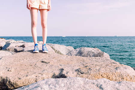 legs of a slim young girl in sneakers standing on the rocks by the sea, copy space for text